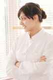 Smiling brunette in smock looking to window Stock Photo