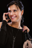 Smiling brunette speaks by mobile phone Royalty Free Stock Image