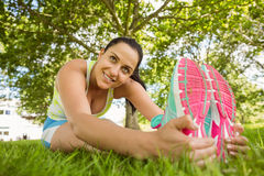 Smiling brunette in sportswear stretching on the grass Stock Images