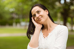 Smiling brunette standing and thinking Royalty Free Stock Image