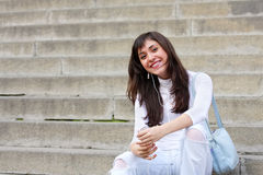 Smiling brunette on stone steps Royalty Free Stock Photography