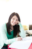 Smiling brunette student doing her homework Stock Photography