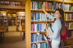 Smiling brunette student picking out book Stock Images