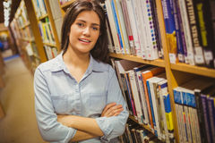 Smiling brunette student standing next to bookshelves with arms crossed Stock Photo