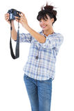 Smiling brunette taking picture with her camera Royalty Free Stock Image