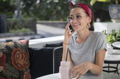 Smiling brunette talking on phone sitting outdoors, young model posing at table royalty free stock photography