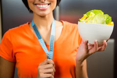 Smiling brunette with tape measure around neck holding bowl of salad Stock Images
