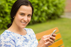 Smiling brunette using her smartphone Royalty Free Stock Photo