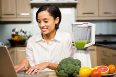 Smiling brunette using laptop and preparing smoothie. In the kitchen Royalty Free Stock Image