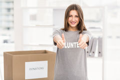 Smiling brunette volunteer doing thumbs up Stock Images