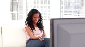 Smiling brunette watching the television stock video footage