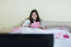 Smiling brunette wearing bathrobe watching tv Royalty Free Stock Image