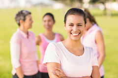 Smiling brunette wearing pink for breast cancer in front of friends Stock Photography