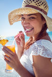 Smiling brunette wearing straw hat and drinking a cocktail Royalty Free Stock Image