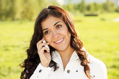 Smiling brunette on white cellphone Stock Photography