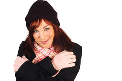 Smiling brunette in winter clothes. Smiling brunette wearing a winter hat, gloves, scarf and jacket isolated against a white background Royalty Free Stock Photography