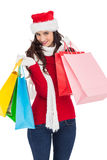 Smiling brunette in winter wear holding shopping bags Stock Images