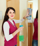 Smiling brunette woman cleaning  mirror Stock Images