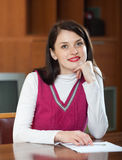 Smiling brunette woman with  documents at table Royalty Free Stock Image