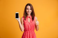 Smiling brunette woman in dress showing blank smartphone screen. And thumb up over yellow background Stock Photography
