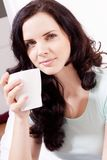Smiling brunette woman drinking black coffee Stock Image