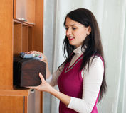 Smiling  brunette woman dusting wooden furiture Royalty Free Stock Image