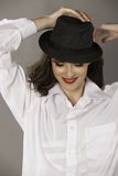 Smiling  brunette woman with hat and red lips. Portrait in color of a beautiful young Caucasian woman wearing dramatic makeup, a white shirt, red lipstick, hat Stock Photography