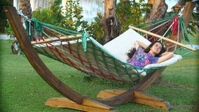 Smiling brunette woman in hat relaxed in the hammock on tropical beach. Young smiling brunette woman in hat relaxed in the hammock on tropical beach stock video
