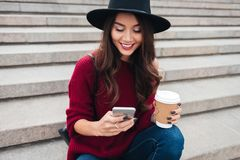 Smiling brunette woman in hat and sweater sitting on stairs. Outdoors with cup of coffee and using her smartphone Royalty Free Stock Images