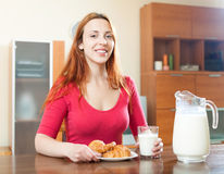 Smiling brunette woman having breakfast with juice in morning at Royalty Free Stock Images