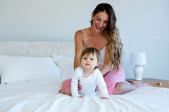 smiling brunette woman holding a cute baby royalty free stock photography