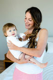 smiling brunette woman holding a cute baby stock images