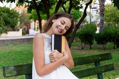 Smiling brunette woman is hugging her favourite book on the bench in the park.  royalty free stock photo