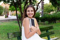 Smiling brunette woman is hugging her favourite book on the bench in the park.  royalty free stock image
