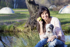 Smiling  brunette woman hugging her white  dog with apple in the hand Stock Photos