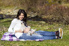 Smiling  brunette woman hugging her white  dog outdoor Stock Photo