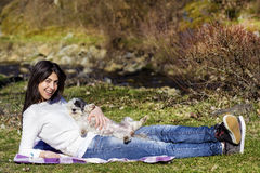 Smiling  brunette woman hugging her white  dog outdoor Royalty Free Stock Images