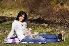 Smiling  brunette woman hugging her white  dog outdoor Royalty Free Stock Image