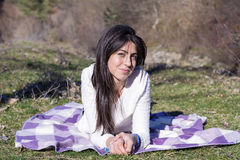 Smiling brunette woman lying on a blanket outdoor Stock Photography