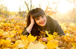 Smiling brunette woman lying on yellow leaves at autumn park Stock Images