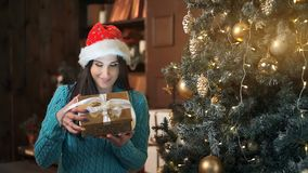 Smiling brunette woman opening gift box over lights of Christmas tree stock video footage