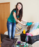 Smiling brunette woman packing suitcase Royalty Free Stock Images