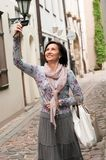 Smiling brunette woman with photo camera in town Royalty Free Stock Photography