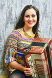 Smiling brunette woman playing the accordion Stock Image