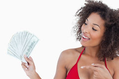 Smiling brunette woman pointing a fan of dollar notes Royalty Free Stock Photography