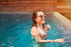 Smiling brunette woman in pool water. Smiling brunette woman in blue pool water. Holiday vacation concept Stock Photography