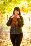 Smiling brunette woman posing at autumn park at sunny day Stock Photography