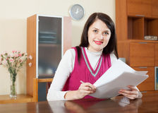 Smiling brunette woman reading document Stock Photography