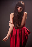 Smiling brunette woman in red dress holding hand on shoulder Stock Photography
