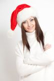 Smiling brunette woman in santa hat Stock Images